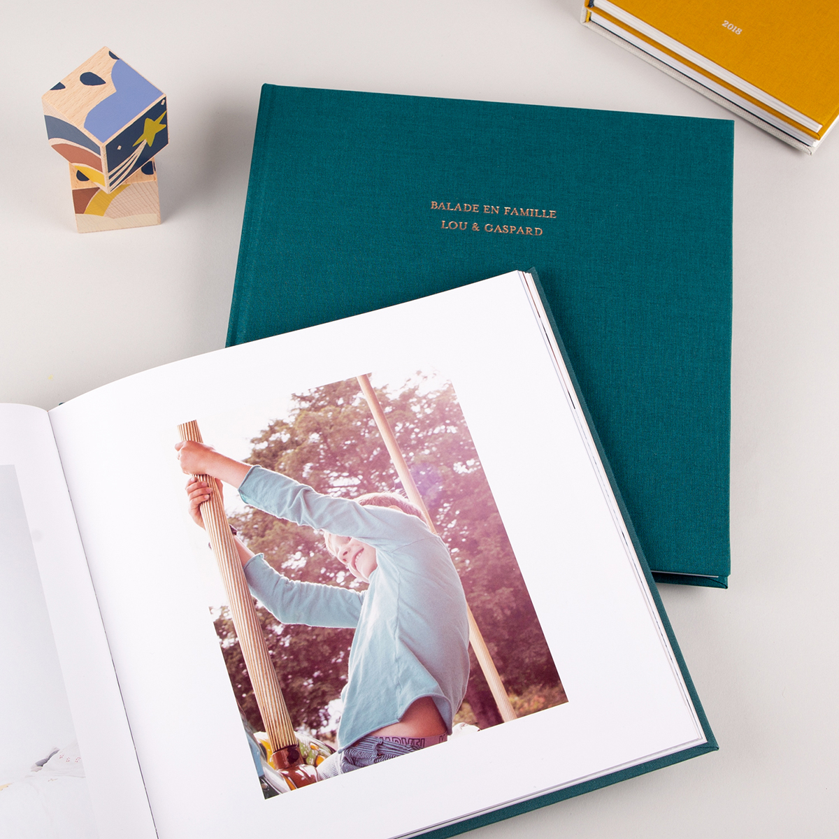 Album vert mis en scène avec des cubes en bois